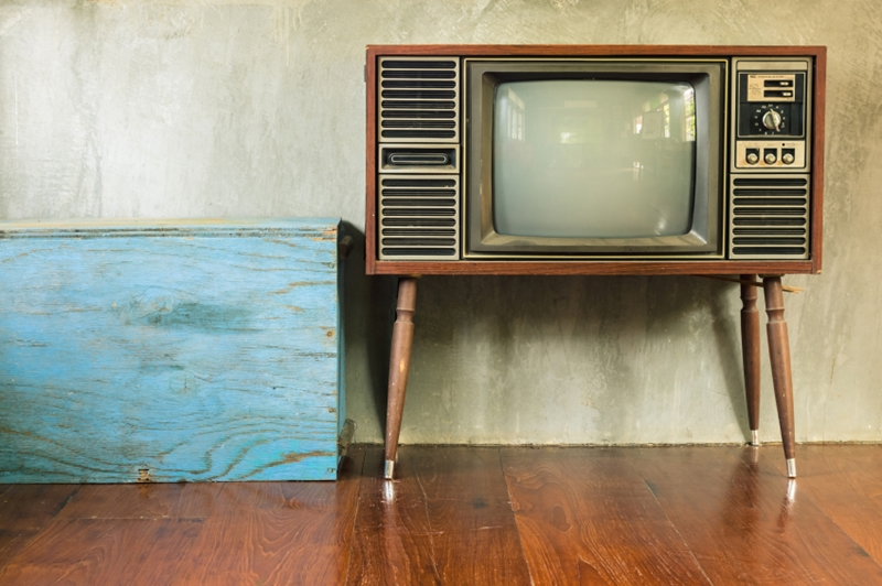 Retro television with blue wood container in the old room